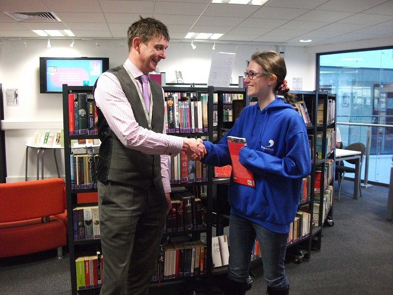 The 'Pyeong Chang 2018 Winter Olympics Quiz' winner being presented with her prize by Jim Temple the Library Manager.